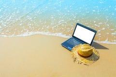 Bärbar dator- eller datoranteckningsbok på havsstranden och vågen - affärstra Arkivfoton