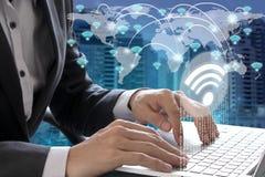 Bärbar dator för affärsmanhandbruk med wifisymbolsanslutning Arkivfoto