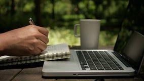 Bärbar dator för bruk för manfreelancer som en märkes- skriver på anteckningsboken och dricker kaffe på trädgården arkivfilmer