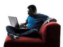 Bärbar dator för dator för mansoffasoffa beräknande Fotografering för Bildbyråer