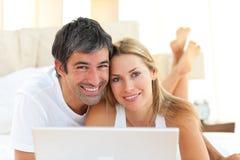 bärbar dator för ho för underlagpar som förälskad ligger genom att använda royaltyfri fotografi
