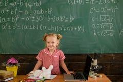 Bärbar dator för skolaelevbruk som tar fram online-utbildning i klassrum Lilla flickan har kurs på anteckningsboken för avstånd arkivfoto