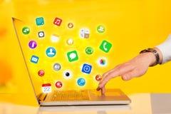 Bärbar dator för trycka på för hand modern med mobila app-symboler och symboler Arkivfoto