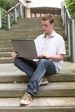 Bärbar dator 4 för ung man Arkivbild