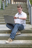 Bärbar dator 5 för ung man Arkivfoto