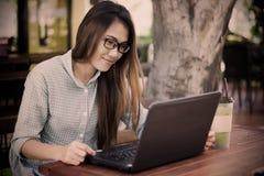 bärbar dator genom att använda kvinnabarn Arkivfoton
