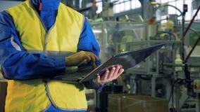 Bärbar dator i händerna av en man som arbetar i en fabrik stock video