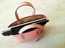 Bärbar dator i rosa kvinnas handväska Arkivfoto