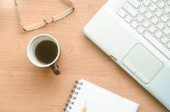 Bärbar dator, kopp kaffe, exponeringsglas och anteckningsbok på skrivbordet Royaltyfri Fotografi