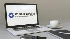 Bärbar dator med den China Construction Bank logoen på skärmen Tolkning för ledare 3D för modern arbetsplats begreppsmässig Fotografering för Bildbyråer