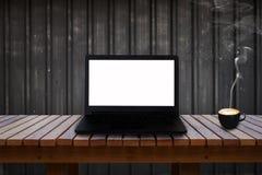 Bärbar dator med den isolerade skärmen på trätabellen och en kopp kaffe Royaltyfria Foton