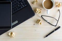 Bärbar dator med den skrynkliga papper och koppen kaffe på trätabellen Arkivfoton