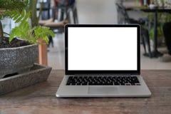 Bärbar dator med den tomma skärmen på tabellen Begreppsmässig workspace, bärbar datordator med den tomma vita skärmen på tabellen arkivbild
