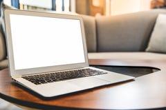 Bärbar dator med den tomma skärmen på tabellen i vardagsrum royaltyfria bilder