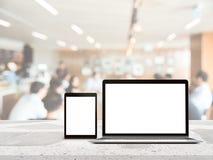 Bärbar dator med den tomma skärmen som förläggas på den vita trätabellen med metting bakgrund för suddig affär för montageprodukt Royaltyfri Bild