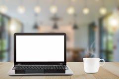 Bärbar dator med den tomma vita skärmen och den varma kaffekoppen på tappningträtabellen på suddig coffee shopbakgrund Arkivfoto