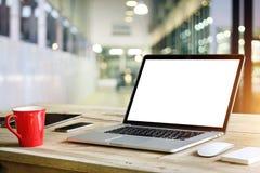 Bärbar dator med den tomma vita skärmen på tabellen i regeringsställning Royaltyfri Fotografi