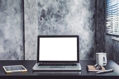 Bärbar dator med den vita tomma skärmen, den vita koppen kaffe, minnestavlan, anteckningsboken, pennan och exponeringsglas på skr Royaltyfri Foto