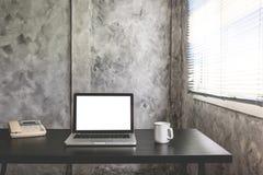 Bärbar dator med den vita tomma skärmen, den vita koppen kaffe och telefonen på skrivbordet Fotografering för Bildbyråer