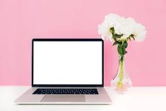 Bärbar dator med den vita tomma skärmen och blommor i vas på tabellen på rosa bakgrund Åtlöje upp Royaltyfri Bild