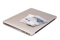 Bärbar dator med dollar- och europengar Fotografering för Bildbyråer