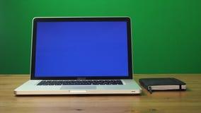 Bärbar dator med en grön skärm och svartnotepad på tabellen Grön skärmbakgrund lager videofilmer
