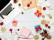 Bärbar dator med julpynt och gåvor på trätabellen arkivbilder