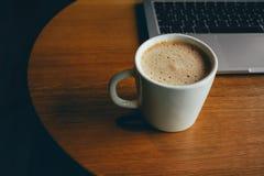 Bärbar dator med koppen av nytt kaffe Arkivfoto