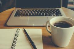 Bärbar dator med koppen av nytt kaffe Arkivbild