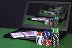 Bärbar dator med pengar- och pokerchiper Fotografering för Bildbyråer