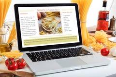 Bärbar dator med recept på en tabell med pasta och grönsaker Arkivfoton