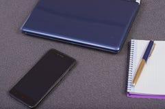 Bärbar dator med smartphonen och anteckningsboken som tar anmärkningar royaltyfri fotografi