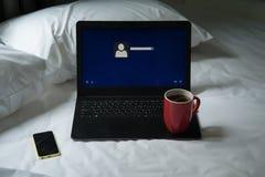 Bärbar dator, mobiltelefon och en kopp kaffe på sängen Fotografering för Bildbyråer