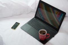 Bärbar dator, mobiltelefon och en kopp kaffe på sängen Arkivfoto