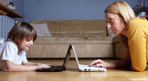 bärbar dator mother liten son två som fungerar Royaltyfri Foto