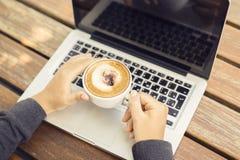 Bärbar dator och cappuccino på en trätabell Royaltyfria Bilder