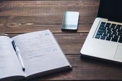 Bärbar dator och dagbok på skrivbordet Arkivbild