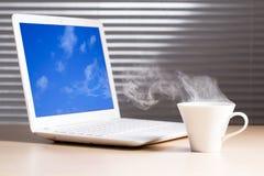Bärbar dator och en kopp kaffe Arkivbild