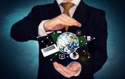 Bärbar dator och jordklot för affärsperson hållande Arkivfoto
