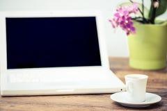 Bärbar dator och kaffe på skrivbordet arkivfoton
