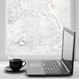 Bärbar dator och kaffe på vinterfönster Royaltyfri Foto