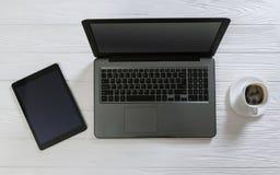 Bärbar dator- och kaffekopp på det vita träskrivbordet Arkivfoton