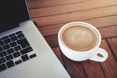 Bärbar dator- och kaffekopp på träskrivbordet Royaltyfri Bild