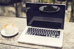 Bärbar dator och kopp av cappuccino på en trätabell Fotografering för Bildbyråer