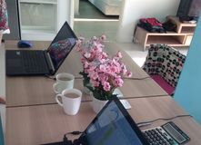 Bärbar dator och kopp kaffe på tabellen royaltyfria bilder
