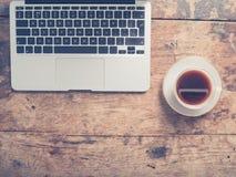 Bärbar dator och kopp kaffe på tabellen royaltyfria foton