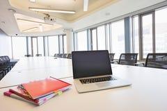 Bärbar dator och mappar på den tomma konferenstabellen i idérikt kontor Royaltyfria Foton