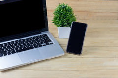 Bärbar dator och mobil på trä av den bruna tabellen idébilden för begreppet 3d framförde Falsk U Arkivfoton