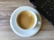 Bärbar dator och nytt kaffe arkivfoto