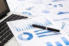 Bärbar dator och penna med blåa affärsdiagram, grafer, statistik och